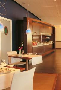 Salle du restaurant. Meuble petit déjeuner en placage Sapelli verni naturel, portes coulissantes rainurés, plan en granit.
